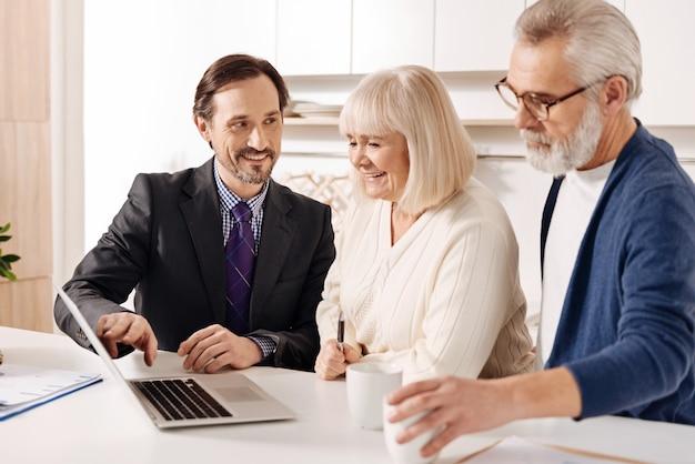 Asegurando una elección rentable. agente de bienes raíces inteligente sincero optimista que se reúne con una pareja mayor de clientes mientras presenta el plan de la casa y usa una computadora portátil