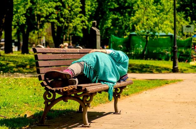 Asentamiento femenino sin hogar del refugiado y sueño en el banco en parque público el día de primavera.