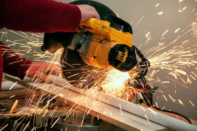 Aserrado trabajador industrial, corte y soldadura de metal con muchas chispas afiladas.