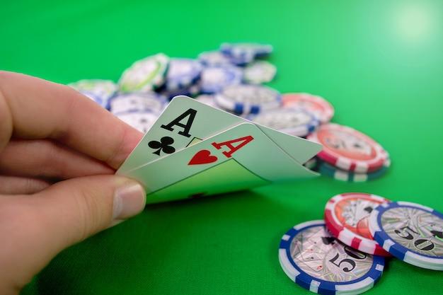 Ases en la mano de póker con fichas