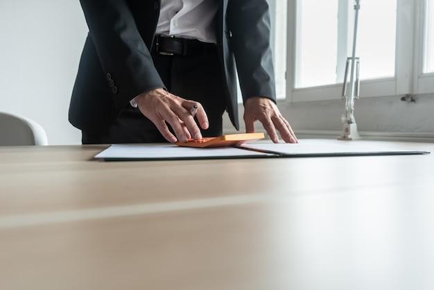 Asesor financiero de pie en su escritorio haciendo cálculos rápidos usando la calculadora mientras revisa un informe.