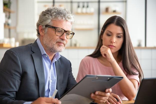 Asesor legal maduro enfocado que lee y analiza el documento del cliente