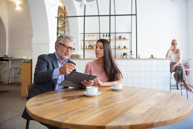 Asesor legal maduro enfocado que lee, analiza y explica el documento a la clienta