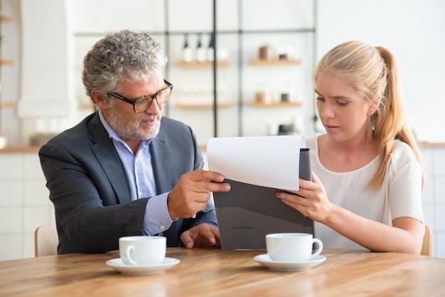 Asesor legal maduro que lee el documento y explica los detalles a un cliente joven