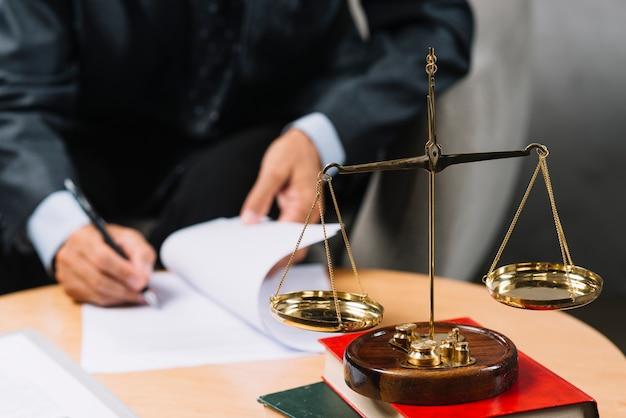 Asesora legal firmando el contrato con escala de justicia en primer plano.