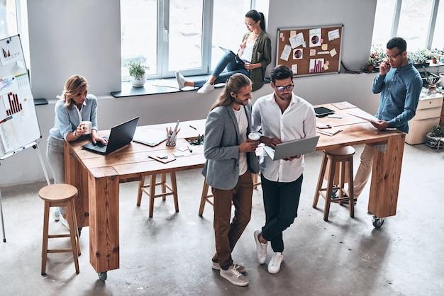 Asesoramiento empresarial. vista superior de los jóvenes modernos que trabajan juntos mientras pasan tiempo en la oficina