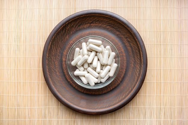 Ashwagandha (whitania somnifera) cápsulas de hierbas vegetales en un plato marrón