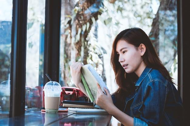 Asia adolescente sentado solo leyendo un libro en la barra de café.