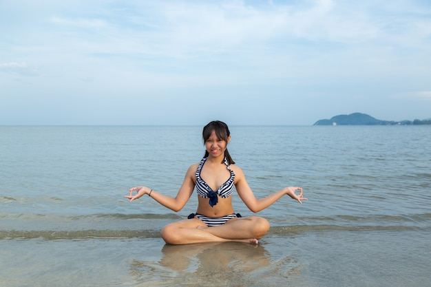 Asia adolescentes vistiendo bikini sentada meditación en la playa.