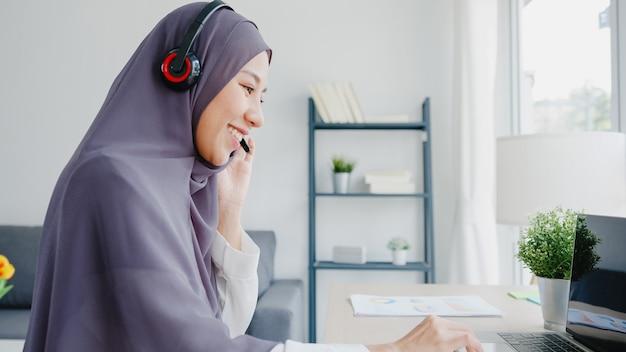 Asia dama musulmana usa audífonos ver seminario web escuchar curso en línea comunicarse por videoconferencia en casa.