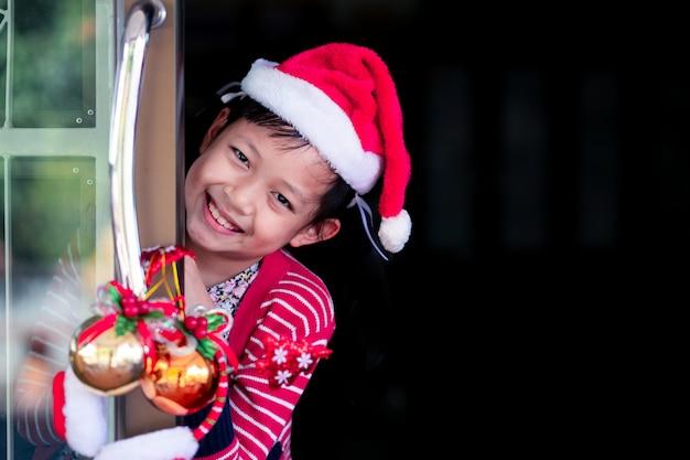 Asia hermosa niña sonriente detrás de la puerta