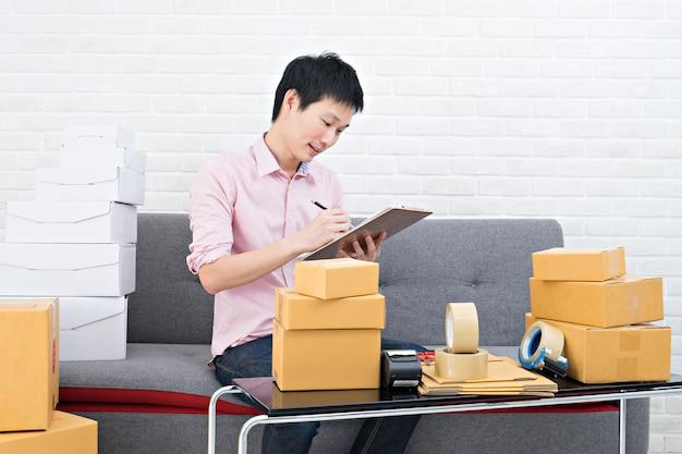 Asia hombre trabajando pyme de negocios en línea en casa. concepto de negocio en línea