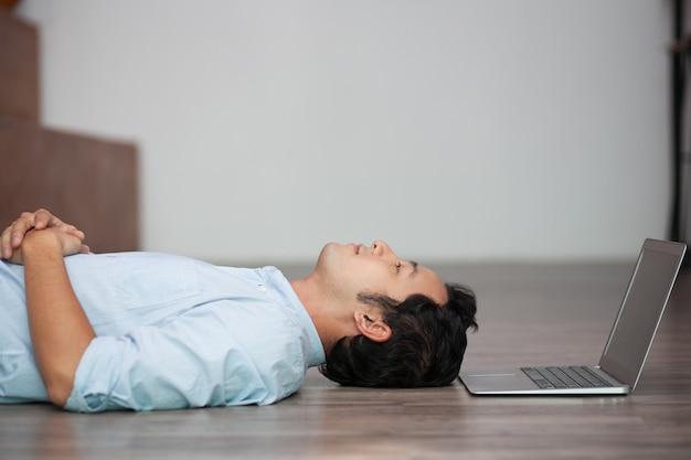 Asia hombre tumbado en el suelo en su computadora portátil