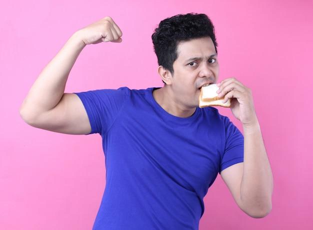 Asia los hombres comen pan y se sienten fuertes sobre fondo rosa en estudio.