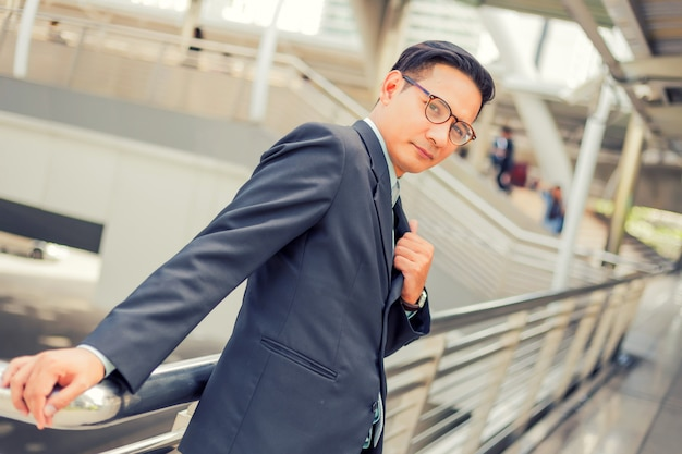 Asia joven hombre de negocios frente al moderno edificio en el centro concepto de jóvenes empresarios