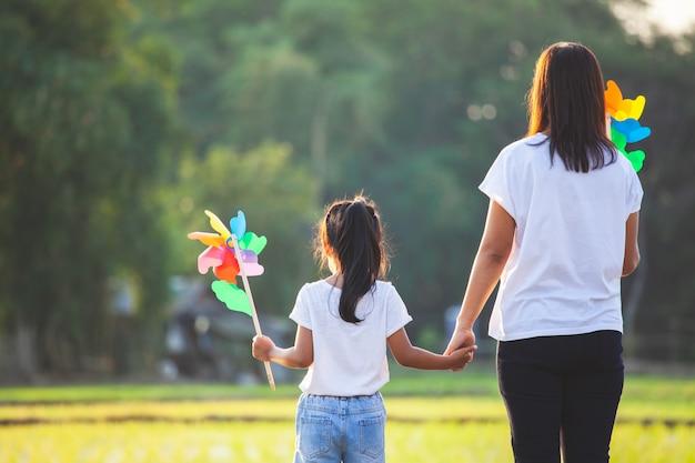 Asia madre e hija cogidos de la mano y jugando con aerogeneradores de juguete juntos en el campo de arroz