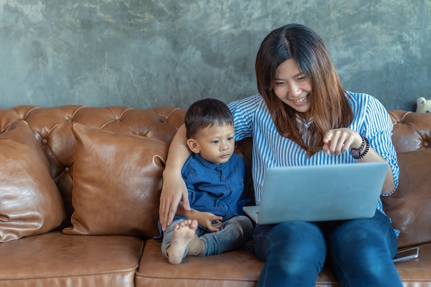 Asia madre soltera con hijo buscando dibujos animados