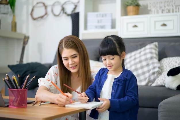 Asia mamá e hija felices están usando la computadora portátil para estudiar en línea a través de internet en casa. concepto de e-learning durante el tiempo de cuarentena.