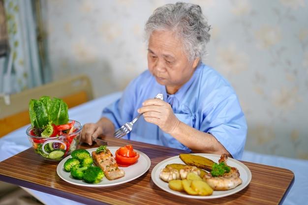 Asia mayor o anciana anciana mujer paciente desayunando