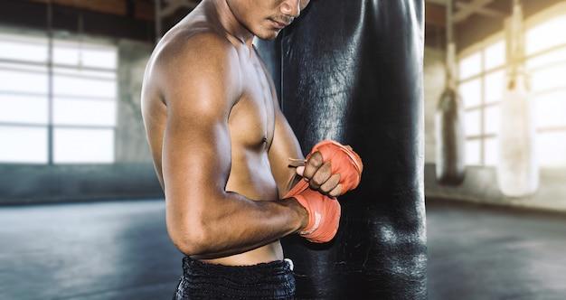 Asia muay thai con vendas de boxeo con guantes de boxeo preparándose para el entrenamiento de combate.