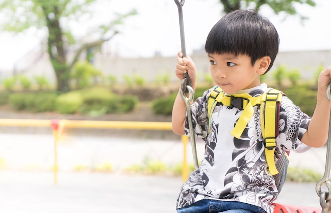 Asia muchacho columpiándose en el patio de recreo con espacio de copia brillante