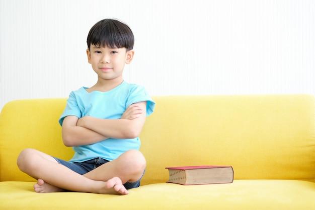Asia muchacho está sentado en el sofá amarillo con gran libro rojo.