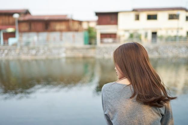 Asia mujer sentada al lado del río