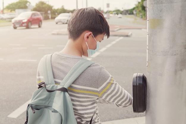 Asia preadolescente interpolación jovencito usando su codo presionando el botón del semáforo