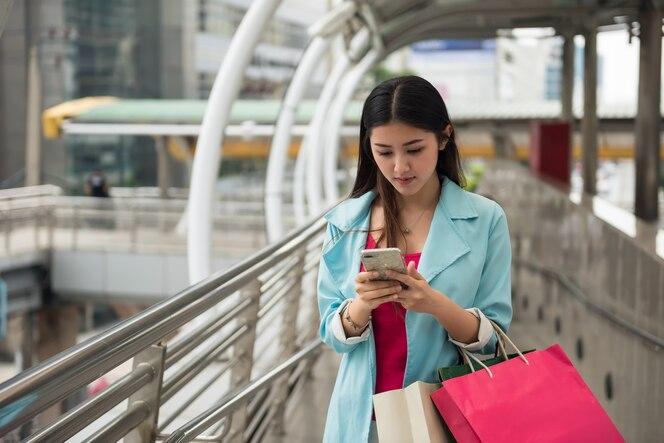 Asia turista mujer navegando por mapa de la tienda por teléfono inteligente