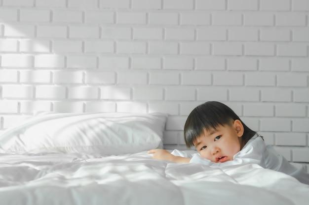 Asian boy japanese children vistiendo camisa blanca en dormitorio blanco en sala blanca