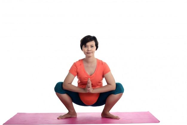Asiática embarazada haciendo yoga