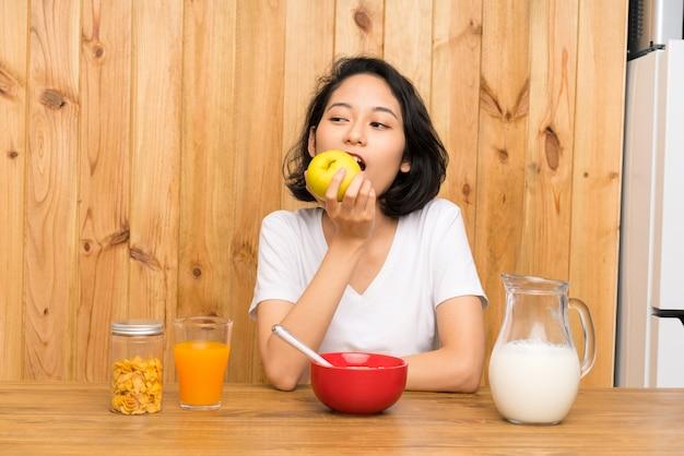 Asiática joven desayunando y con una manzana