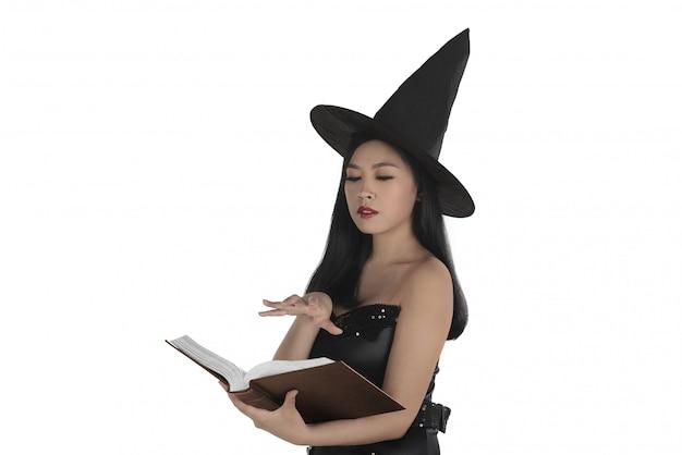 Asiática sexy bruja creando un hechizo en el libro.