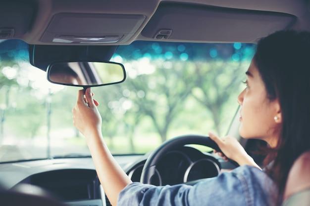Las asiáticas están ajustando el espejo retrovisor del coche.