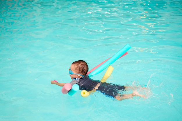 Asiático 2 - 3 años niño pequeño niño toma clase de natación, niño aprende a flotar solo con fideos de piscina, niño con juguete y pateando las piernas en la piscina cubierta