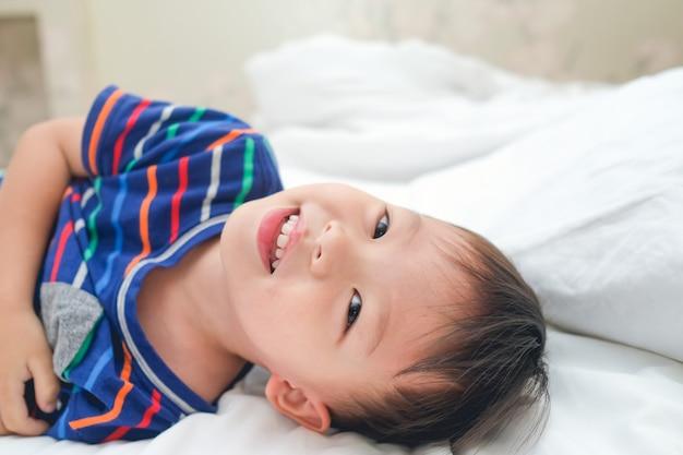 Asiático 3-4 años niño pequeño niño despertando en la cama, alegre niño acostado en la cama mirando a la cámara