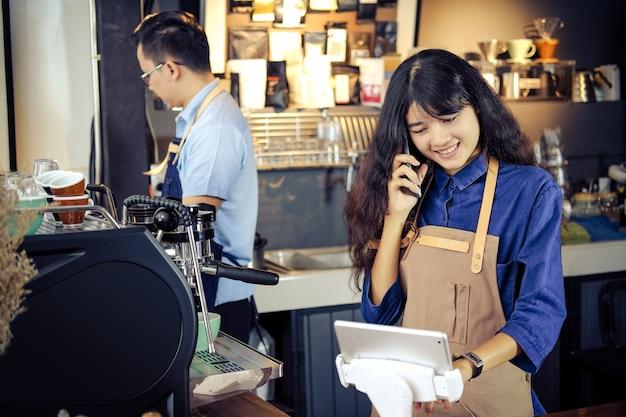 Asiático barista hablando por teléfono en su tienda