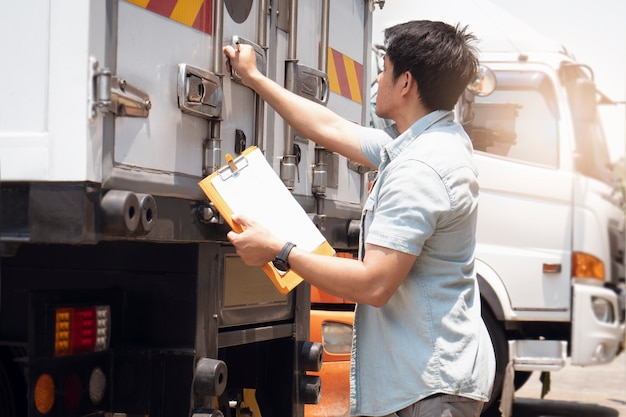 Asiático, un conductor de camión con portapapeles está comprobando la puerta de acero del contenedor de seguridad del camión contenedor. transporte de carga, logística y transporte.