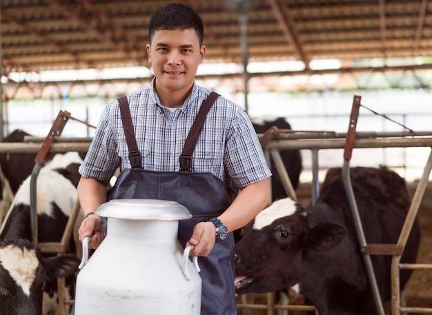 El asiático del granjero del retrato está sosteniendo un envase de leche en su granja.