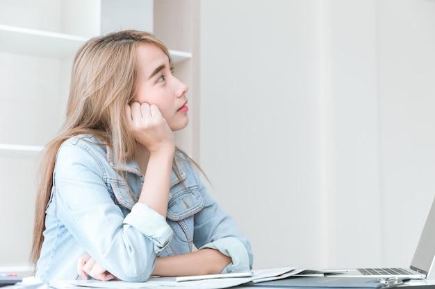 Asiático joven empleado pensando o desatento imaginación sueño mientras trabajaba en la oficina