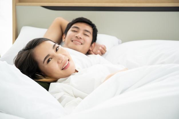 Asiático marido y mujer descansando en la cama juntos en la mañana.