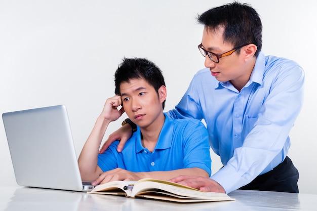 Asiático padre e hijo aprendiendo en casa para la escuela