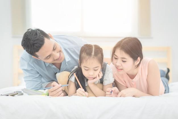 Asiático padre y madre enseñando a su hija hija a estudiar en casa.