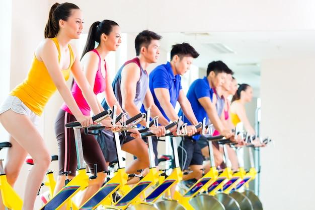 Los asiáticos en bicicleta de spinning en el gimnasio de fitness