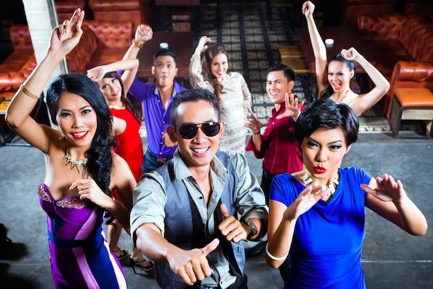 Los asiáticos de fiesta en la pista de baile en la discoteca