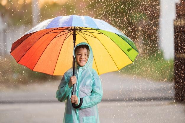Asiáticos, niños extendiendo paraguas jugando bajo la lluvia, ella lleva ropa impermeable.