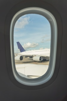 Asiento de avión y ventana dentro de un avión.