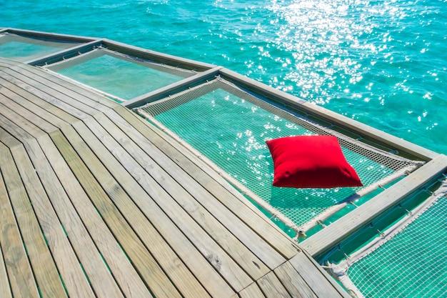 Asiento neto de vacaciones en la isla tropical de maldivas y la belleza del mar con los arrecifes de coral.