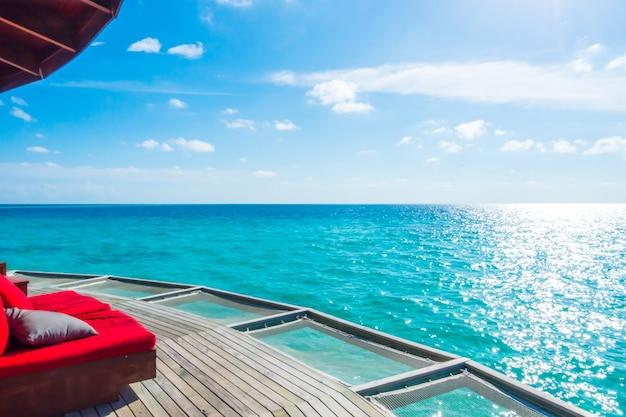 Asiento de red de vacaciones en la isla tropical de maldivas y la belleza del mar con los arrecifes de coral