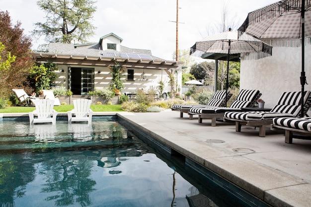 Asientos de madera junto a una piscina con sombrillas.